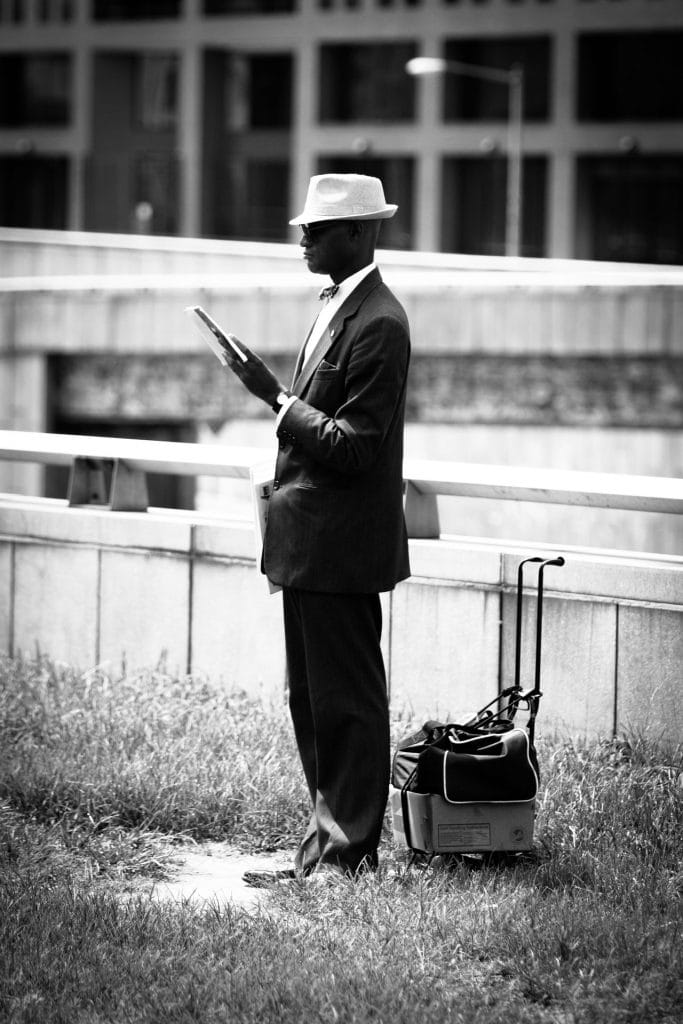 in Washington on the intersection of Massachusetts av and 2nd av was this man reading the newspaper that he is about to sell to passing cars.